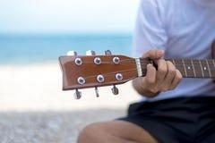 生活方式人 关闭弹经典吉他的英俊的人坐海滩在假期,夏天 库存照片