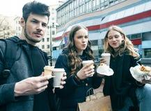 生活方式和人概念:吃在城市街道上的两个女孩和人便当一起获得乐趣,饮用的咖啡 免版税库存照片