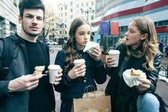 生活方式和人概念:吃在城市街道上的两个女孩和人便当一起获得乐趣,饮用的咖啡 库存照片