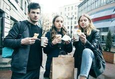 生活方式和人概念:吃在城市街道上的两个女孩和人便当一起获得乐趣,饮用的咖啡 免版税库存图片