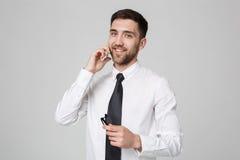 生活方式和企业概念-一个英俊的商人的画象喜欢谈与手机 查出的空白背景 Co 免版税库存图片
