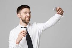 生活方式和企业概念-一个英俊的商人的画象喜欢采取一selfie与拿走咖啡 被隔绝的w 免版税库存图片