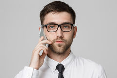 生活方式和企业概念-一英俊的商人严肃谈话的画象与手机 查出的空白背景 库存图片