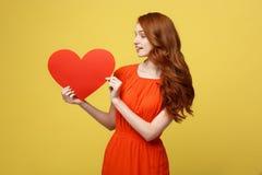 生活方式和假日概念-拿着大红色心脏的橙色美丽的礼服的画象年轻愉快的红色头发妇女 库存图片