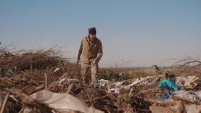 生活方式在转储喝寻找在包裹的衣物食物与走的肮脏的男性无家可归的饥饿的人去 影视素材