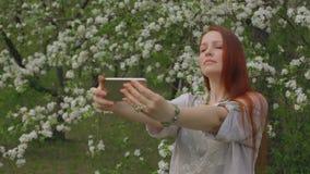 生活方式妇女在一个开花的庭院里采取在电话的一selfie 影视素材
