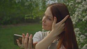 生活方式妇女在一个开花的庭院里采取在电话的一selfie 股票录像