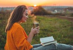 生活方式室外休闲的概念在秋天 女孩在有一个热杯子的格子花呢披肩读了书 秋天 日落 舒适 免版税库存图片