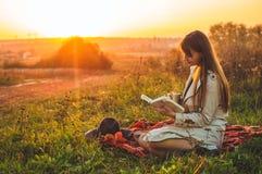 生活方式室外休闲的概念在秋天 有帽子的女孩在有一个热杯子的格子花呢披肩读了书 秋天 日落 舒适 免版税库存照片