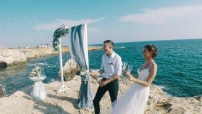 生活方式录影:愉快的新婚佳偶在海附近庆祝在岩石的一婚礼,飞溅香槟 股票视频