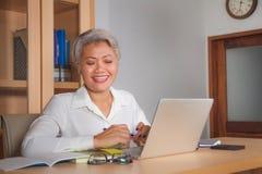 生活方式有吸引力和愉快的成功的中部办公室画象变老了工作在手提电脑书桌微笑的亚裔妇女 免版税库存照片