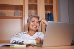 生活方式有吸引力和愉快的成功的中部办公室画象变老了工作在手提电脑书桌微笑的亚裔妇女 库存图片