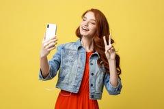 生活方式概念:摆在年轻快乐的妇女,当拍摄在闲谈的聪明的电话照相机与她时 免版税库存照片