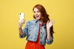 生活方式概念:摆在年轻快乐的妇女,当拍摄在闲谈的聪明的电话照相机与她时 库存照片