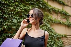 生活方式概念 关闭太阳镜和黑礼服微笑的可爱的年轻深色头发的白种人妇女 库存图片