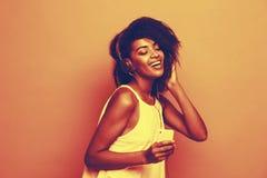 生活方式概念-画象美丽的非裔美国人的妇女快乐听到在手机的音乐 淡色 免版税库存图片