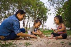 生活方式画象使用与沙子的妈妈儿子和女儿,滑稽的亚洲家庭在公园 免版税库存照片
