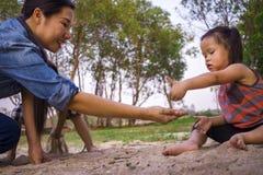 生活方式画象使用与沙子的妈妈儿子和女儿,滑稽的亚洲家庭在公园 免版税库存图片
