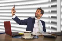 生活方式画象年轻愉快和成功商人工作轻松在现代办公室由窗口计算机书桌谈的sel 免版税库存图片