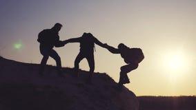 生活方式配合帮助商务旅游剪影概念 小组游人借一个帮手攀登峭壁 股票视频