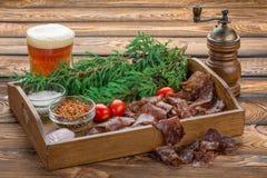 生涩的牛肉用啤酒 圣诞节静物画生涩用香料、大盐、西红柿和一个树枝在一个木盘子 库存照片