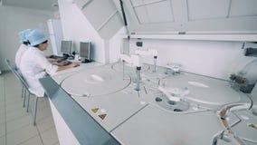 生物化学的分析仪在与几一起使用实验室专家在一个配药实验室 影视素材