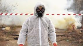 生物危害品衣服和气体的人走到用抽烟报道的被污染的区域 股票视频