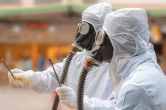 生物危害品衣服和防毒面具的两个人 库存照片