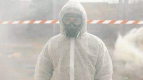 生物危害品衣服和防毒面具的人在抽烟站立 股票录像