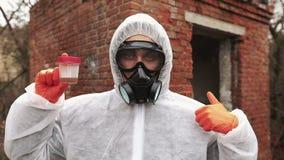 生物危害品衣服和防毒面具的人显示污水和非语言的标志 股票视频