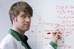 生物科技英俊的学员whiteboard年轻人 图库摄影