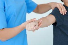 生理治疗师与诊所的患者一起使用 免版税库存照片