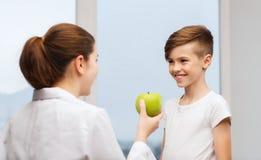 医生用绿色苹果和诊所的愉快的男孩 免版税图库摄影