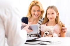 医生的小女孩有她的母亲的 库存图片