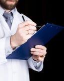 医生的特写镜头手,他采取在患者的病史的笔记 图库摄影