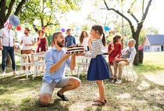生给蛋糕家庭庆祝或生日聚会的一个小女儿 免版税库存照片