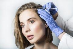 医生美学家做顶头秀丽射入给美丽的女性患者 库存图片