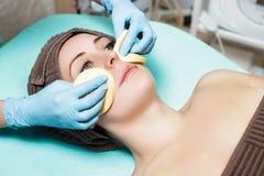 医生美容师洗涤有海绵的皮肤妇女 完善的清洁-整容术治疗skincare面孔 免版税库存图片