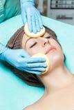 医生美容师洗涤有海绵的皮肤妇女 整容术治疗skincare面孔 瓣程序玫瑰温泉 库存图片