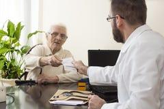 医生老年医学专家的老妇人 有一名患者的老年医学专家医生在他的办公室 图库摄影