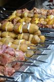 生肉和土豆在金属串被种植 烹调烤肉串的过程 俄国和乌克兰阵营食物 免版税库存照片