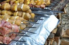 生肉和土豆在金属串被种植 烹调烤肉串的过程 俄国和乌克兰阵营食物 库存图片