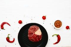 生肉小腿用辣椒和蕃茄在一白色painte 免版税库存照片