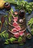 生肉放在架子上的羊羔,与烹调成份的准备 免版税库存照片