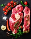 生肉牛排用西红柿、辣椒、大蒜、油和草本在黑暗的石头,具体背景 空位 库存图片