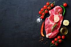 生肉牛排用西红柿、辣椒、大蒜、油和草本在黑暗的石头,具体背景 空位 库存照片