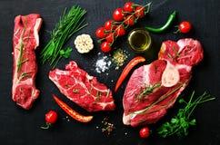 生肉牛排用西红柿、辣椒、大蒜、油和草本在黑暗的石头,具体背景 空位 图库摄影