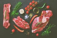 生肉牛排用西红柿、辣椒、大蒜、油和草本在黑暗的石头,具体背景 空位 免版税库存图片