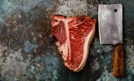生肉精选了头等烘干年迈的牛排丁骨牛排和砍肉刀 库存照片