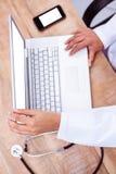 医生膝上型计算机使用 图库摄影